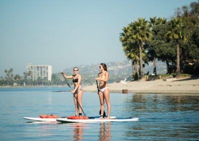Two girls on stand up paddle board rentals from Action Sport Rentals